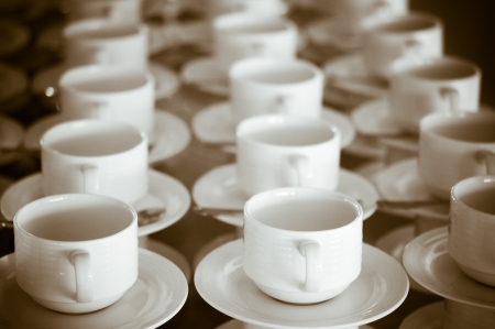 Many rows of pure white cup and saucer designed in vintage retro style. Note: the image contains grain as an element of style. photo