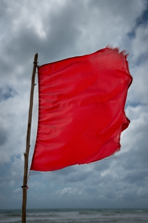 Red warning flag at a beach with storm clouds on background photo