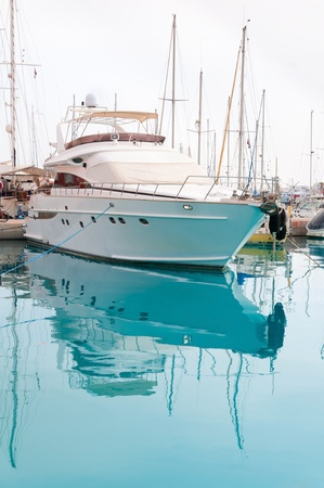 prow: White yacht in a moorage with clean blue water
