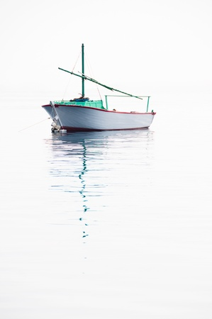 industry moody: Lonely small fishing boat on very calm sea with smooth surface flowing together with sky
