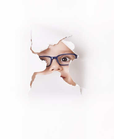 Cuus kid in spectacles looks through a hole in white paper Stock Photo - 15071627