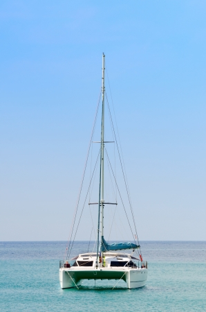 catamaran: Luxury white sail catamaran boat in the sea with blue sky  Stock Photo