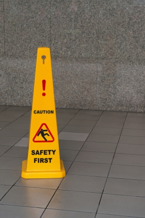 Caution wet floor sign on tiled floor with stone wall on background Stock Photo - 15751924