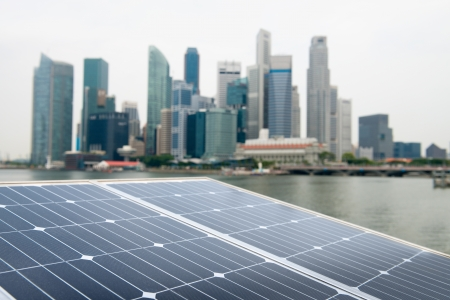Solar panel with modern city and skyscrapers on background