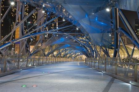 singapore city: Modern empty futuristic bridge against the background of night city  Editorial