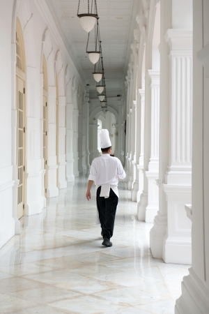 famous industries: Singapore - September 08, 2012:Waiter in classical uniform in corridors of the Raffles Hotel. It is the oldest hotel in Singapore