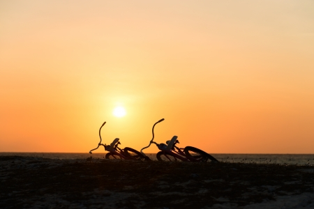 Two lying bikes silhouettes at the sunset on a beach photo