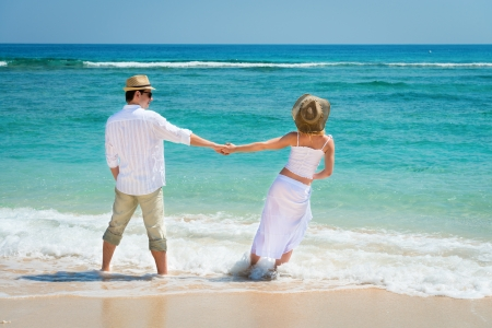 Rear view of romantic young couple in hats and white dress in blue sea at the beach
