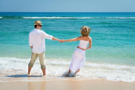 luna de miel: Vista trasera de la joven pareja rom�ntica en sombreros y vestido blanco en el mar azul en la playa Foto de archivo