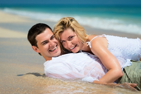 Happy embracing young couple lie on sand of a tropical beach with blue sea on background photo