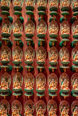 Many small Buddhist statues on lotus flowers with red wall on background  Selective focus on front  Stock Photo - 15916549