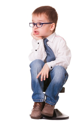 angry child: Angry kid in shirt and jeans sits on small chair, on white background
