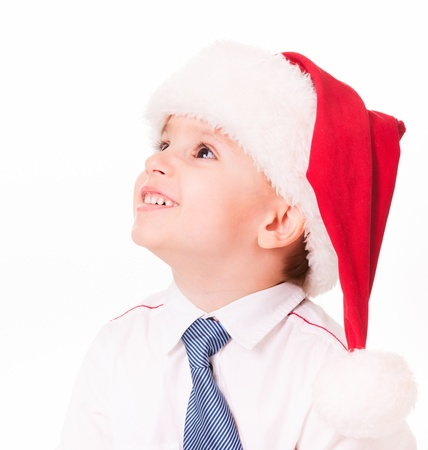 Happy little boy in shirt and tie in santa hat looks up  Isolated on white  Stock Photo - 15891009