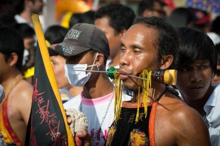 durchstechen: Phuket, Thailand - 21. Oktober 2012: Anh�nger des Vegetarian Festival ist Mah Song, Person, die die Geister der G�tter l�dt, um ihren K�rper zu besitzen. Mah Song tragen aufw�ndige Kost�me und durchbohren ihre Wangen und Zungen mit allen m�glichen Dingen.