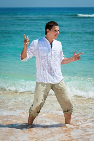 immensely: Happy young man dancing at the tropical beach in blue sea water