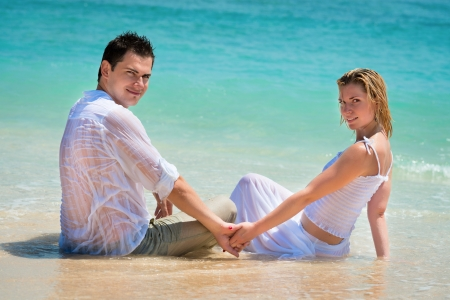 Young couple enjoying their holiday on the beach on blue tropical beach photo