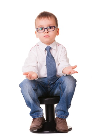 Confused clever kid in jeans and shirt sitting on small chair isolated on white background Imagens