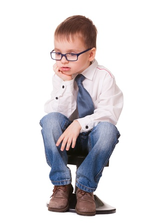 Very sad clever kid in jeans and shirt sitting on small chair isolated on white background photo