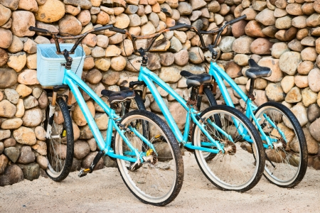 Three old, rusty blue bicycles parked near a stone wall  photo