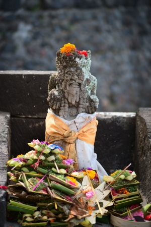 Typical outdoor Balinese Hindu statue with a lot of offerings  photo