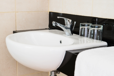 Ceramic hand wash basin in a hotel with chrome water mixer tap, white towel and two glasses photo