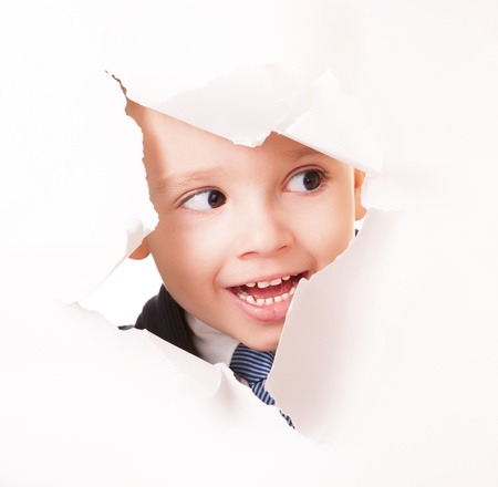 Cuus smiling kid spying through the hole in the wooden wall Stock Photo - 16128198