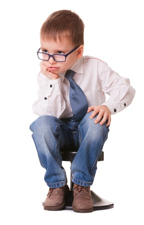 Serious clever kid in jeans and shirt sitting on small chair isolated on white background photo