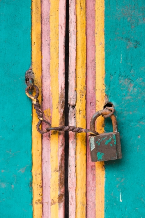 Vintage lock and chain on an old colorful wooden door Stock Photo - 16385607