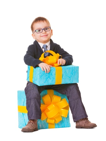Small boy in spectecles with two big presents on white background photo