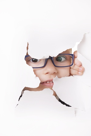 Curious kid in spectacles looks through a hole in white paper Stock Photo - 16305256