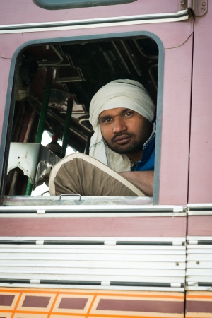 AGRA, INDIA - NOVEMBER 15: Typical Indian driver in white turban in the cabin of his truck  on Nov 15, 2012 in Agra, India