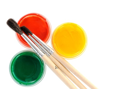 Yellow, red and green paints with paint brushes over white background  photo