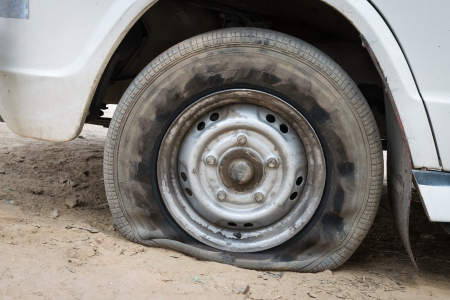 Deflated damaged tyre on white car wheel