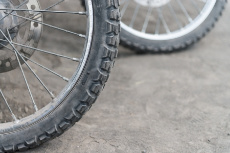 Off-road motorcycle tires on dusty ground  Selective focus on the front part  photo
