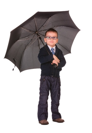 Calm boy in black clothes standing under big black umbrella isolated on white Stock Photo - 16984808