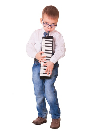 Preschool boy in glasses, jeans and white shirt playing melodica, isolated on white background Stock Photo - 16984805