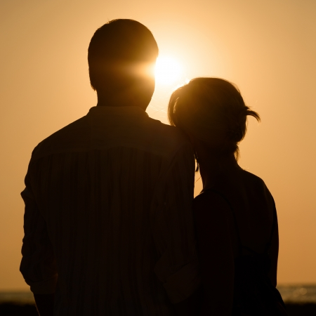 Silhouette of loving couple over orange sunset background