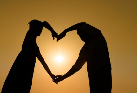 Silhouette of loving couple with hands in heart shape over orange sunset background  photo