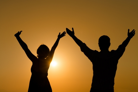 Silhouette of loving couple raise their hands with enjoy over orange sunset background  photo