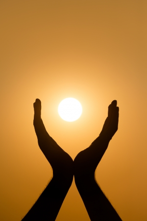 Hands holding the sun at yellow sunset background