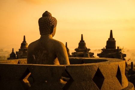 Buddha statue in open stupa in Borobudur, or Barabudur, temple Jogjakarta, Java, Indonesia at sunrise. It is a 9th-century Mahayana temple and the biggest  Buddhist Temple in Indonesia. photo