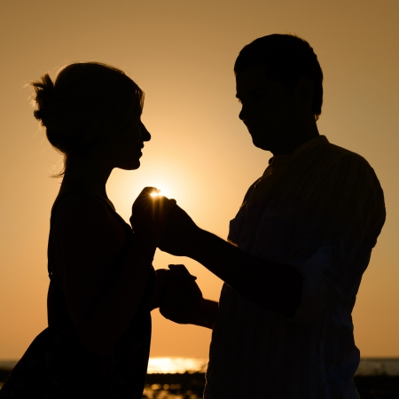Silhouette of loving couple over orange sunset background  photo