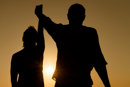 rely: Silhouette of loving couple raise their hands together over orange sunset background