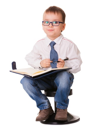 Small clever kid with organizer notebook and pen looking in camera. Isolated on white background. photo