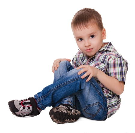 unworried: Small serious sitting boy in jeans and sneakers isolated on a white background  Stock Photo