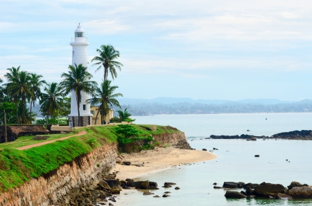 White lighthouse on fortified stone wall with cloudy sky background, Galle, Sri Lanka photo