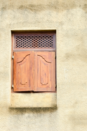 Small wooden window with close shutters on yellow wall  photo