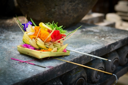 Traditional balinese offerings to gods in Bali with flowers and aromatic sticks photo