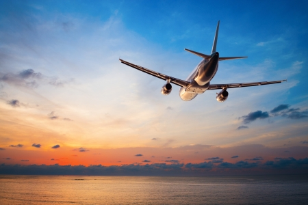 holiday: Airplane flying above tropical sea at sunset  Stock Photo