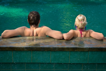 wife of bath: Back view of couple relaxing in a swimming pool on a poolside in tropical resort Stock Photo